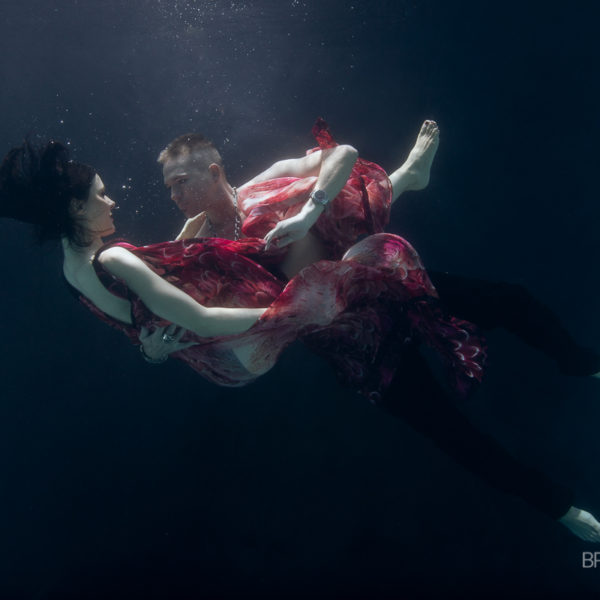 woman and man underwater embracing